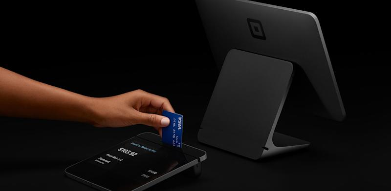 A customer uses a chip reader built into Square Register