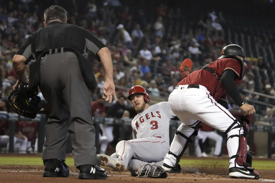 Los Angeles Angels' Taylor Ward (3) scores a run in between umpire Rob Drake and Arizona Diamondbacks catcher Carson Kelly in the second inning during a baseball game, Sunday, June 13, 2021, in Phoenix. (AP Photo/Rick Scuteri)