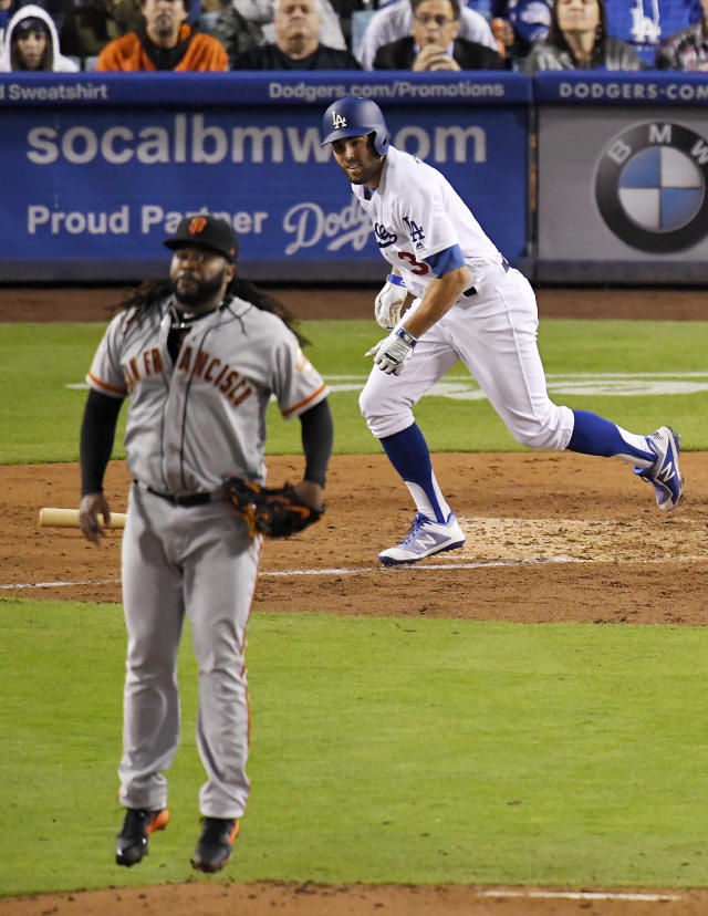 San Francisco Giants starting pitcher Johnny Cueto, left, jumps as Los Angeles Dodgers' Chris Taylor hits a single to break up Cueto's no-hitter during the seventh inning of a baseball game Saturday, Dec. 31, 2016, in Los Angeles. (AP Photo/Mark J. Terrill)
