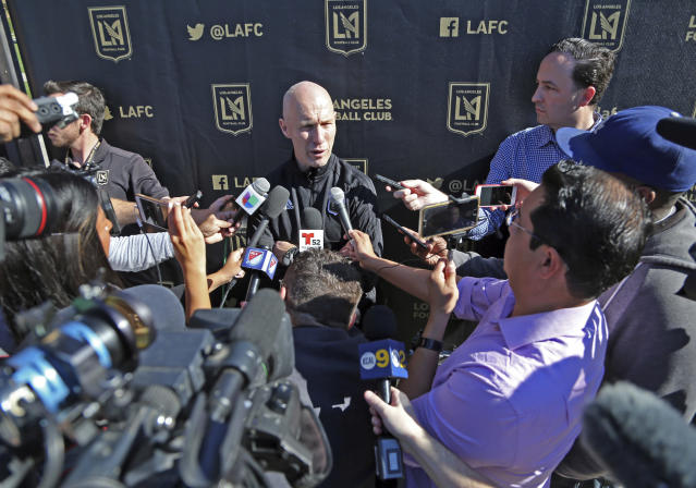 Head coach Bob Bradley, center, talks with reporters during the introduction of players and coaches at the first training camp of the Los Angeles Football Club MLS soccer team on the campus of UCLA in Los Angeles, Monday, Jan. 22, 2018. (AP Photo/Reed Saxon)