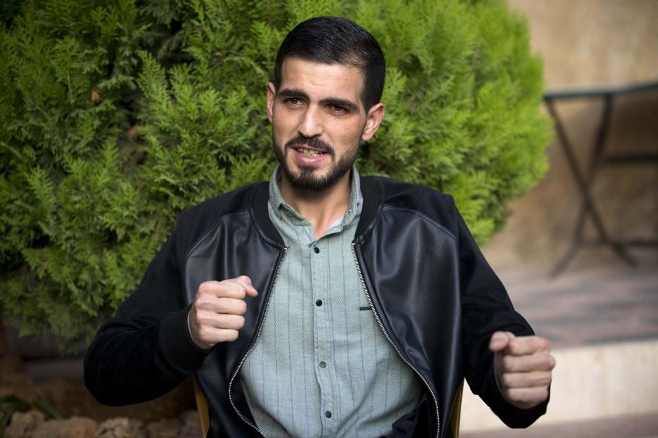Palestinian Karam Qawasmi, who was shot in the back by Israeli forces in an incident caught on video last year, gestures as he gives an interview in the West Bank city of Hebron, Sunday, Nov. 10, 2019. In his first interview since the video emerged last week, Qawasmi said he was run over by a military jeep, then beaten for several hours before troops released him, only to shoot him in the back with a painful sponge-tipped bullet as he walked away. (AP Photo/Majdi Mohammed)