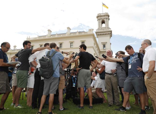 Tennis - Australian Open - Melbourne, Australia, January 29, 2018. Roger Federer of Switzerland is surrounded by members of the media during the men's singles winner's photoshoot at the government house in Melbourne, Australia. REUTERS/Issei Kato