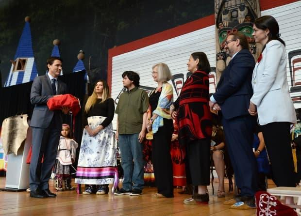 Prime Minister Justin Trudeau, left, holds a copy of the final report from the closing ceremonies of the National Inquiry into Missing and Murdered Indigenous Women and Girls in Gatineau, Que., on June 3, 2019.  (Adrian Wyld/Canadian Press - image credit)