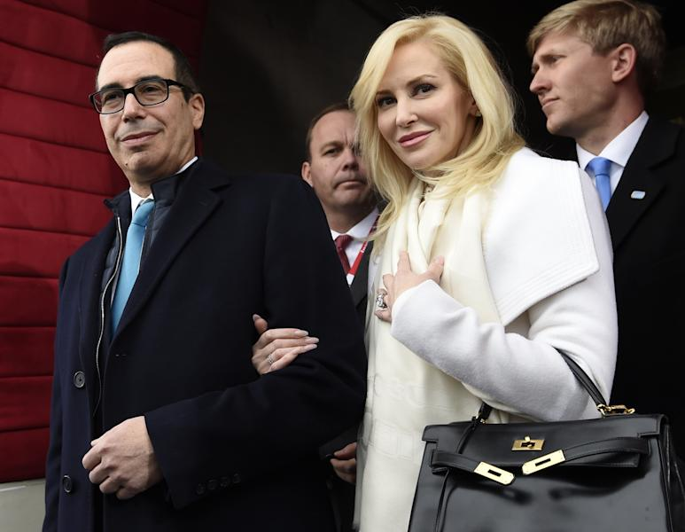 """FILE - In this Friday, Jan. 20, 2017, file photo, then Treasury Secretary-designate Stephen Mnuchin and his then-fiancee, Louise Linton, arrive on Capitol Hill in Washington, for the presidential inauguration of Donald Trump. Linton responded to a social media critic on Aug. 21, 2017, telling the mother of three that that she was """"adorably out of touch."""" Mnuchin and Linton were married in June. (Saul Loeb/Pool Photo via AP, File)"""