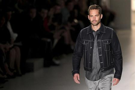 U.S. actor Walker presents a creation from Colcci's 2013/2014 summer collection during Sao Paulo