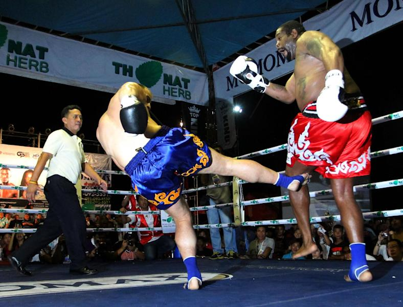 Former heavyweight boxing champion Riddick Bowe of the U.S., right, gets a kick on the leg by Levgen Golovin of Russia, center, during their World Muay Thai or Kick Boxing Super Heavyweight Championships fight in Pattaya, Thailand Friday, June 14, 2013. Golovin won the fight in a second round knockout. (AP Photo/Apichart Weerawong)