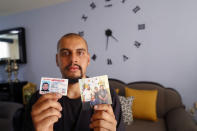 """Jesus Lopez, who was deported from the U.S. last year, holds up his Illinois driver's license and a family snapshot, at his home in Zapopan, Jalisco state, Thursday, May 13, 2021. """"I want to go back because I belong there, that's where I have my friends, my family,"""" said the 25-year-old, once a recipient of the Deferred Action for Childhood Arrivals program that gives protections to immigrants brought to the U.S. as children. (AP Photo/Refugio Ruiz)"""