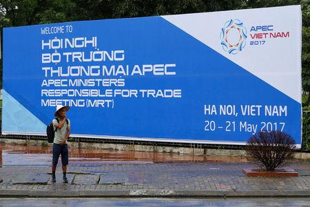 A man stands in front of a banner welcoming APEC trade ministers for a meeting in Hanoi, Vietnam
