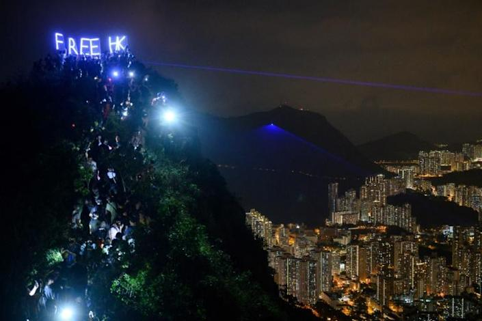 In September hundreds of protesters gathered on Lion Rock shining laser pens and lanterns (AFP Photo/Anthony WALLACE)