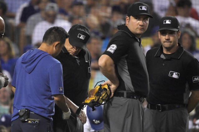 Home plate umpire Larry Vanover, second from left, is attended to by a Los Angeles Dodgers trainer after being hit by ball as Dan Bellino, second from right, and David Rackley look on during the fifth inning of a baseball game between the Dodgers and the Colorado Rockies Monday, Sept. 2, 2019, in Los Angeles. (AP Photo/Mark J. Terrill)