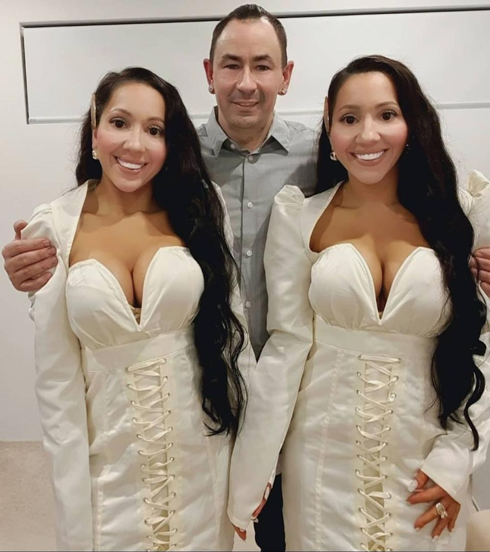 Identical twins Anna and Lucy DeCinque wearing matching white dresses with their shared partner, Ben Byrne