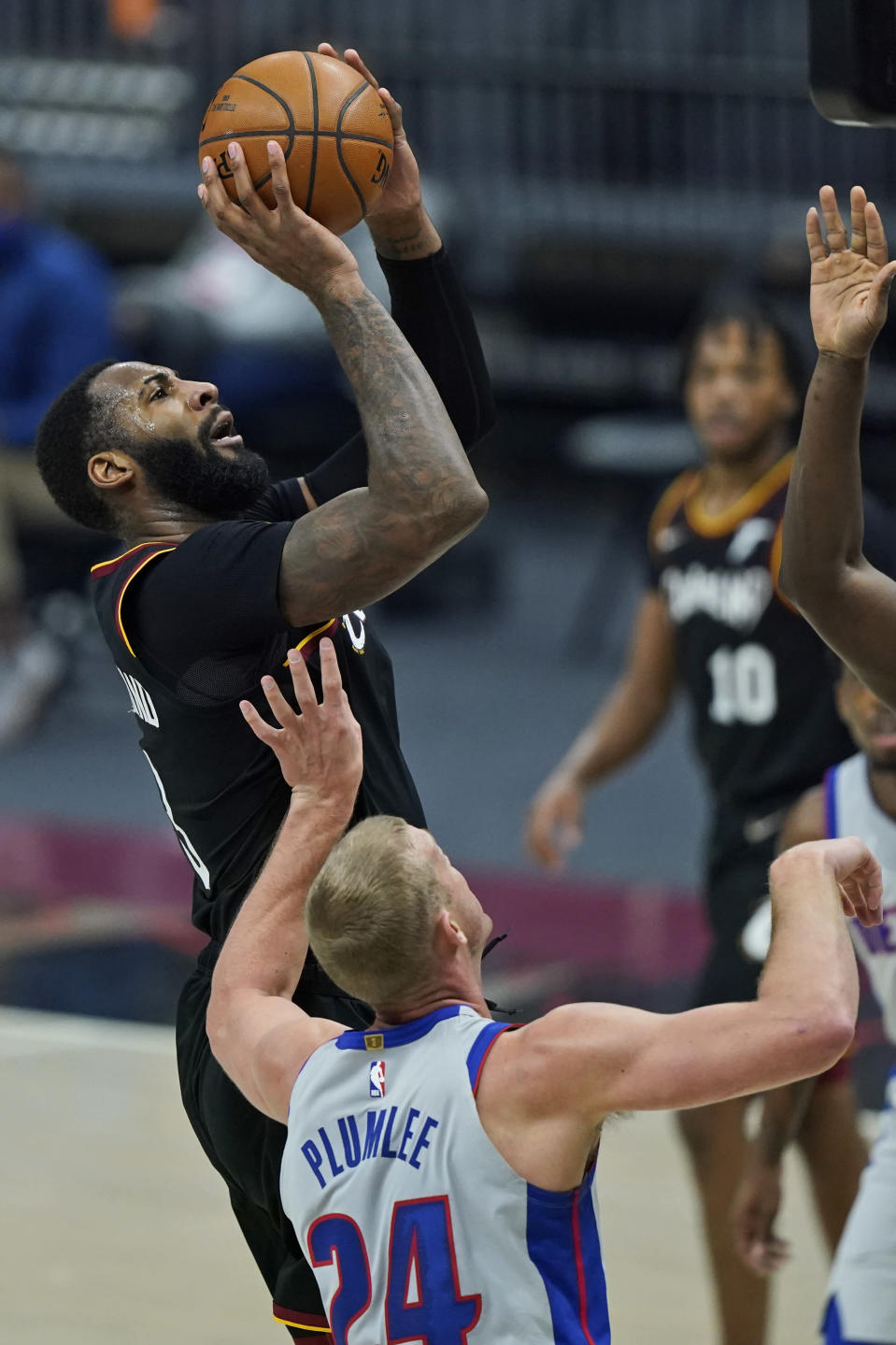 Cleveland Cavaliers' Andre Drummond, left, shoots over Detroit Pistons' Mason Plumlee in the first half of an NBA basketball game, Wednesday, Jan. 27, 2021, in Cleveland. (AP Photo/Tony Dejak)