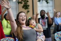 """Hayley Bosarge vies for throws as she holds her daughter Ellie Bosarge, 2, during a parade dubbed """"Tardy Gras,"""" to compensate for a cancelled Mardi Gras due to the COVID-19 pandemic, in Mobile, Ala., Friday, May 21, 2021. (AP Photo/Gerald Herbert)"""