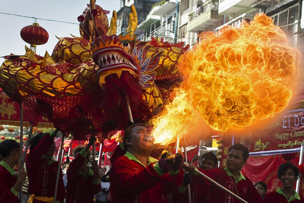 A fire breather blows flames as a troupe performs a traditional dragon dance during the first day of Chinese Lunar New Year in Yangon's Chinatown district on January 28, 2017. (YE AUNG THU/AFP/Getty Images)
