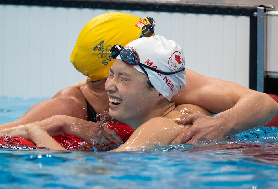 <p>Canada's Margaret MacNeill receives a big hug from Sweden's Sarah Sjoestroem after grabbing gold in the 100m Butterfly for Women at the Tokyo Aquatic Centre on July 26.</p>