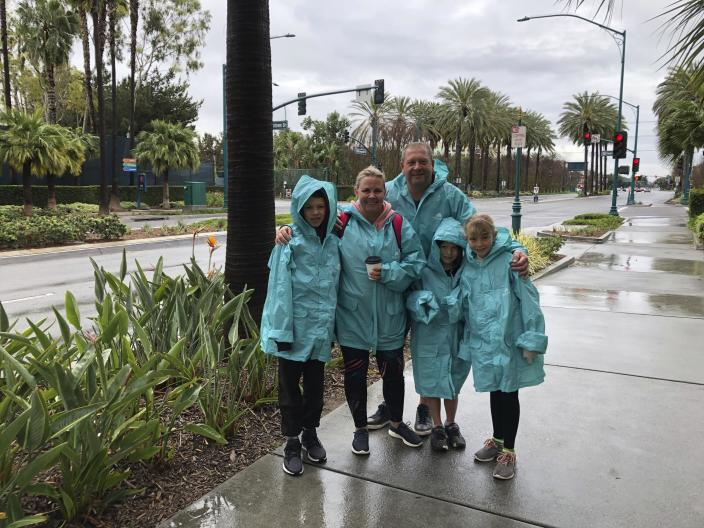 Rochelle Van Eysden, 46, and Jeremy Grice, 45, with children Max, 11; Ava, 9; and Leo, 6 stand outside Disneyland in Anaheim, Calif. on Friday, March 13, 2020. They traveled from New Zealand to Disneyland and planned to stay three days but their trip to the resort was cut short to two by the closure. They're supposed to head on a seven-day cruise this weekend down to Mexico and that trip is also on shaky footing, she said. Disneyland is closing its doors for the rest of the month, shuttering one of California's best-known attractions as the state hurries to stop the spread of the coronavirus. (AP Photo/Amy Taxin)