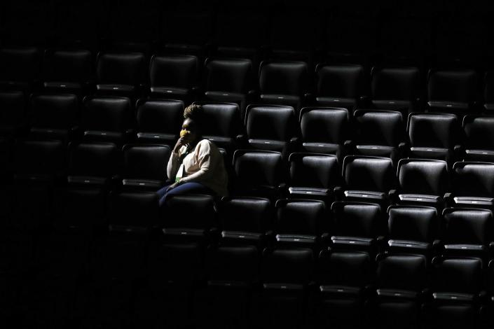 A woman sits in the stands during team introductions before on an NBA basketball game between the Boston Celtics and the Orlando Magic, Sunday, March 21, 2021, in Boston. Some employees of the Celtics and TD Garden were present as a dry run before a limited number of fans will be allowed at games beginning on Monday. (AP Photo/Michael Dwyer)