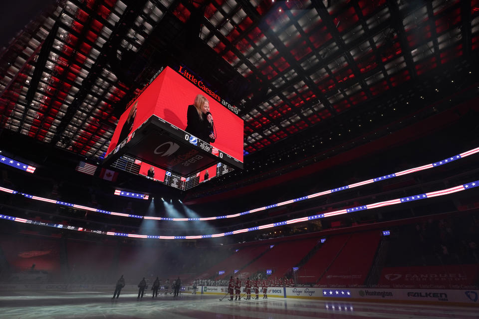 Players stand on the ice during the playing of the national anthem before an NHL hockey game between the Detroit Red Wings and the Tampa Bay Lightning Tuesday, March 9, 2021, in Detroit. (AP Photo/Paul Sancya)