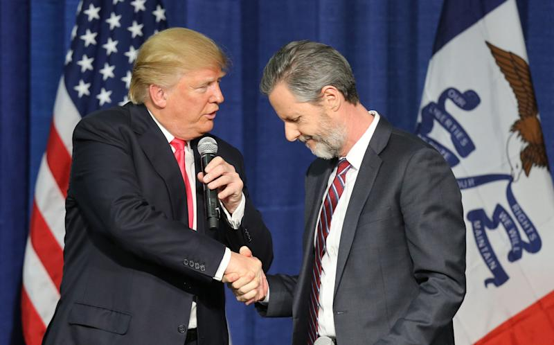 Then-presidential candidate Donald Trump (L) shakes hands with Jerry Falwell Jr. at a campaign rally in Council Bluffs, Iowa, on Jan. 31, 2016.
