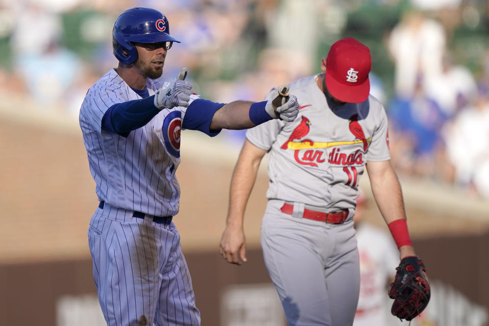 Chicago Cubs' Eric Sogard, left, celebrates after hitting a double as St. Louis Cardinals shortstop Paul DeJong looks down during the third inning of a baseball game in Chicago, Sunday, June 13, 2021. (AP Photo/Nam Y. Huh)