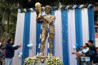 People shower petals on a statue of Argentine soccer great Diego Maradona during a prayer meeting to pay tribute to Maradona, in Kolkata