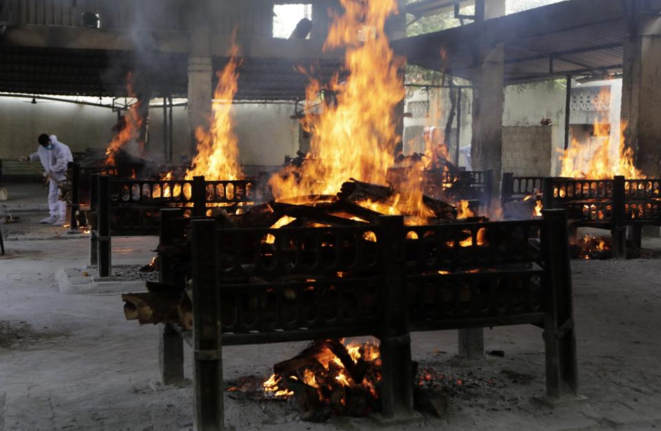 Flames rise from cremation pyres of victims of a fire that broke out in Vijay Vallabh COVID-19 hospital, at Virar, near Mumbai, India, Friday, April 23, 2021. A fire killed 13 COVID-19 patients in a hospital in western India early Friday as an extreme surge in coronavirus infections leaves the nation short of medical care and oxygen. (AP Photo/Rajanish Kakade)