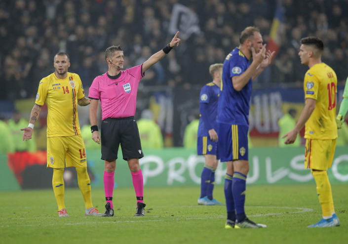 Referee Daniele Orsato stops the game following alleged racist chants against Sweden's Alexander Isak during the Euro 2020 group F qualifying soccer match between Romania and Sweden on the National Arena stadium in Bucharest, Romania, Friday, Nov. 15, 2019. (AP Photo/Vadim Ghirda)