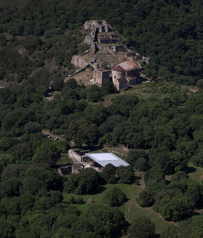 This photo provided by the journal Science shows an aerial view of the Dmanisi excavation site, situated below a medieval Georgian village, where an estimated 1.8-million-year-old skull of a human ancestor was found, the most complete ancient hominid skull found to date. The find is the earliest evidence of human ancestors moving out of Africa and spreading north to the rest of the world, according to a study published Thursday, Oct. 17, 2013, in the journal Science. (AP Photo/F. Javier UrQuijo, Courtesy of Georgian National Museum)