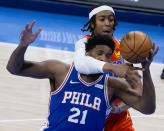 Oklahoma City Thunder center Moses Brown (9) fights for the ball with Philadelphia 76ers center Joel Embiid (21) during the first half of an NBA basketball game, Saturday, April 10, 2021, in Oklahoma City. (AP Photo/Garett Fisbeck)