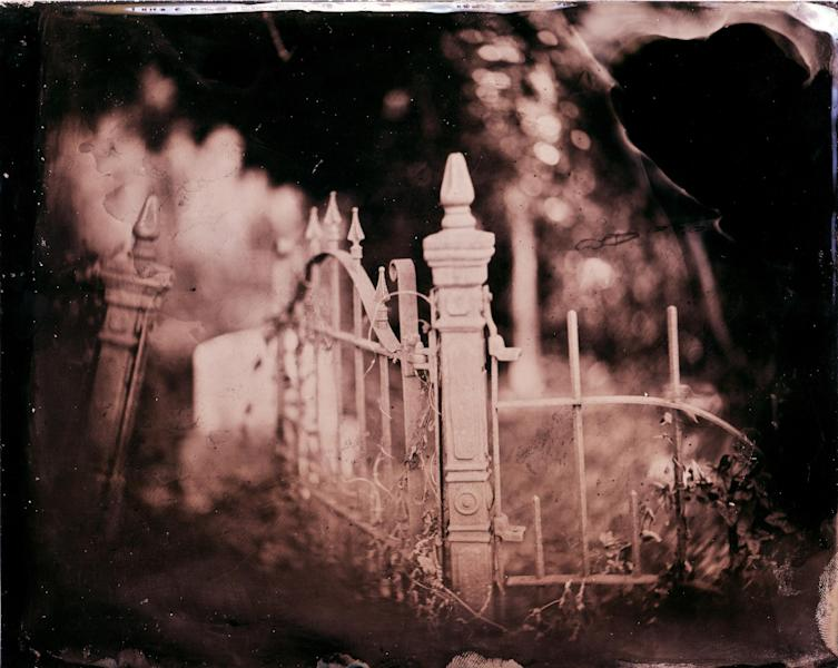 "This 2010 image made by Euphus Ruth Jr. of Greenville, Miss., titled ""He Spoke of Birds,"" features a family grave plot in Bay St. Louis, Miss. ""I was intrigued by the old, rusted wrought-iron gate open, beckoning me to enter,"" recalls Ruth Jr.. ""Birds were flying from an old vase nearby."" Wet plate collodion photography, invented in 1851, has experienced a resurge in recent years as photographers turn to this antiquated method for its moody, haunting images and complicated, hands-on process. (AP Photo/Euphus Ruth Jr.)"