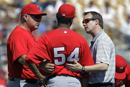 Los Angeles Angels manager Mike Scioscia, left, and trainer Adam Nevala talk with starting pitcher Ervin Santana after he was hit by a ball off the bat of Chicago White Sox's Alexei Ramirez in the second inning of a baseball game Wednesday, March 14, 2012, in Glendale, Ariz. Santana left the game. (AP Photo/Mark Duncan)