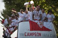 A bus with the Sevilla FC football team parade as they celebrate their Europa League trophy in the streets of Sevilla on May 15, 2014. (GOGO LOBATO/AFP/Getty Images)