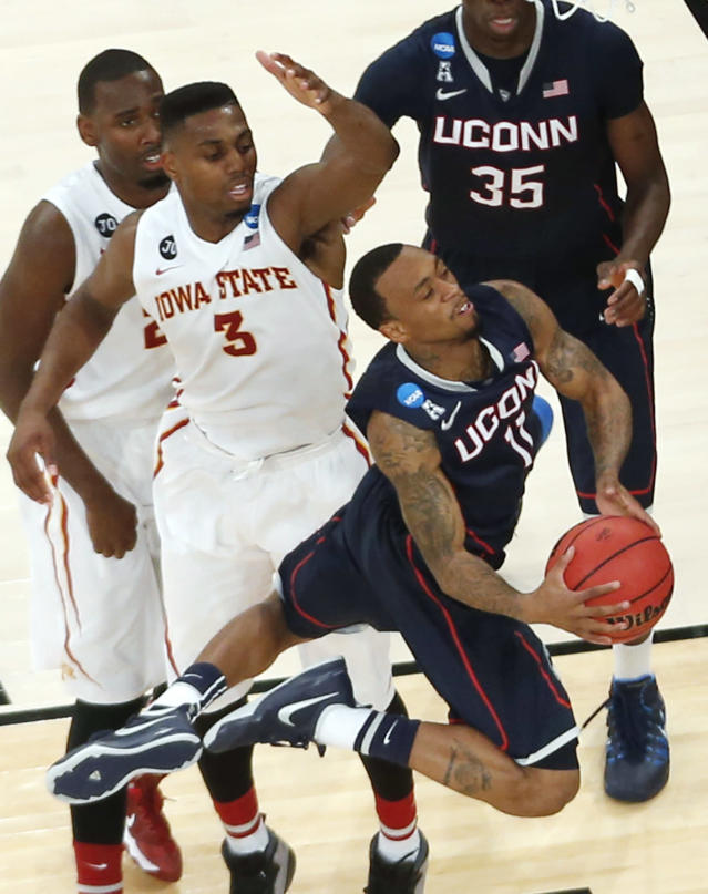 Connecticut's Ryan Boatright drives near Iowa State's Melvin Ejim, center, and Dustin Hogue, left, during the second half in a regional semifinal of the NCAA men's college basketball tournament Friday, March 28, 2014, in New York. (AP Photo/Julio Cortez)