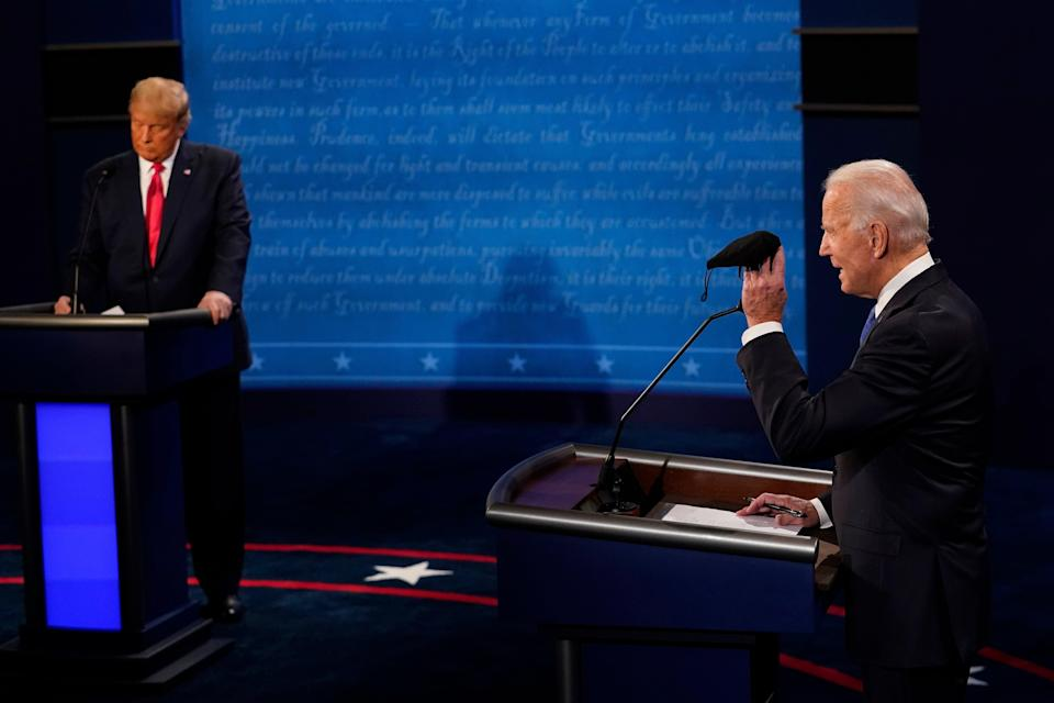 Democratic presidential candidate former Vice President Joe Biden holds up a mask as President Donald Trump takes notes during the second and final presidential debate Thursday, Oct. 22, 2020, at Belmont University in Nashville, Tenn. (AP Photo/Morry Gash, Pool) (AP)