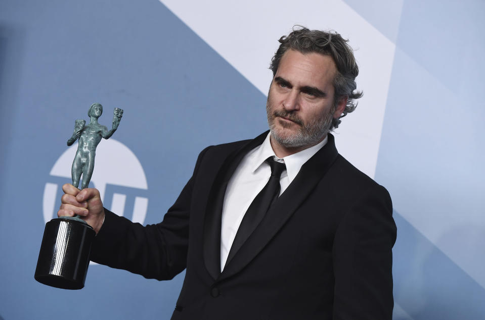 """Joaquin Phoenix poses in the press room with the award for outstanding performance by a male actor in a leading role for """"Joker"""" at the 26th annual Screen Actors Guild Awards at the Shrine Auditorium & Expo Hall on Sunday, Jan. 19, 2020, in Los Angeles. (Photo by Jordan Strauss/Invision/AP)"""