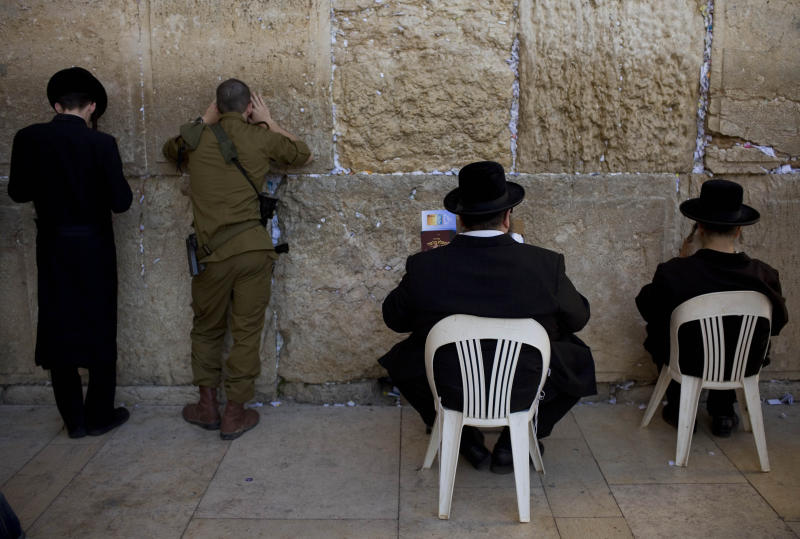 FILE - In this Wednesday, May 5, 2010 file photo, an Israeli soldier, second left, and Ultra-orthodox Jewish men pray at the Western Wall, the holiest site where Jews can pray, in Jerusalem's Old City. A controversial practice that has allowed tens of thousands of young ultra-Orthodox men to avoid compulsory military service has emerged as a looming test for Prime Minister Benjamin Netanyahu's new coalition government and one that could create major mayhem in the Jewish state. (AP Photo/Bernat Armangue, File)