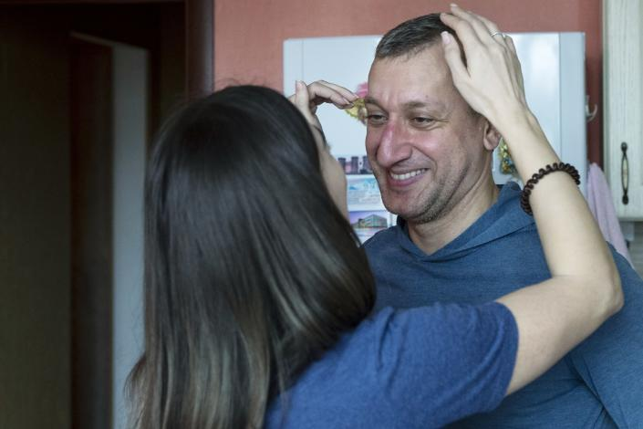 In this photo taken on Saturday, May 16, 2020, Dr. Osman Osmanov is greeted by his wife Saida after a shift at an intensive care unit of Filatov City Clinical Hospital in Moscow, Russia. Moscow accounts for about half of all of Russia's coronavirus cases, a deluge that strains the city's hospitals and has forced Osmanov to to work every day for the past two months, sometimes for 24 hours in a row. (AP Photo/Pavel Golovkin)