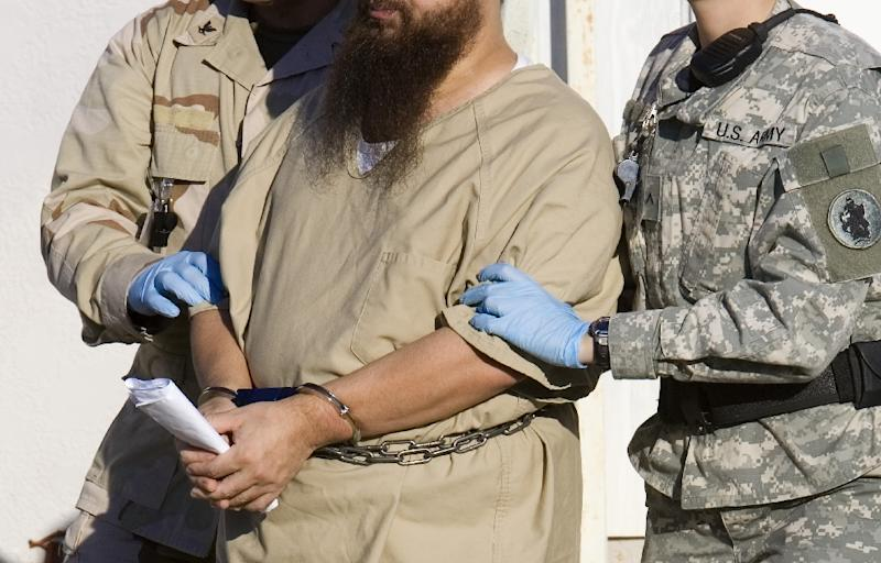 A detainee is escorted by military guards at the US prison at Guantanamo Bay, Cuba, in a 2006 photo