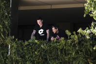 Austria's Dominic Thiem, right, with an unidentified man, stands on the balcony at his accommodation in Adelaide, Australia, Tuesday, Jan. 19, 2021. Australian Open tournament director Craig Tiley defended Serbia's Novak Djokovic for appealing to Australian Open organizers to ease restrictions so players could move to private residences with tennis courts. (Morgan Sette/AAP Image via AP)