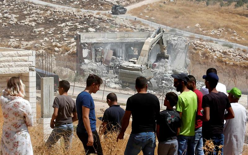 Palestinians watch as Israeli security forces tear down a Palestinian building - AFP