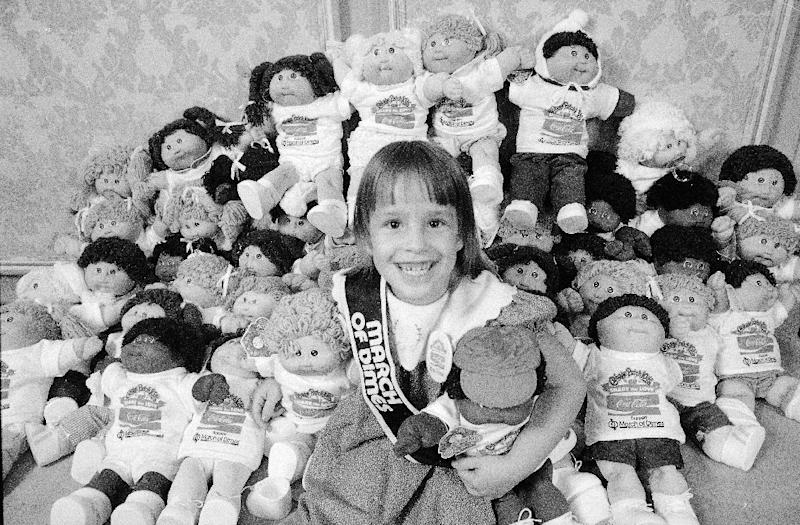 FILE - In this Aug. 30, 1984, file photo, Helen Humphrey, the 1984 National Poster Child for the March of Dimes Birth Defects Foundation, smiles as she holds Cabbage Patch Kids in New York. Created in 1978, plush Cabbage Patch Kids with yarn hair became one of the biggest toy crazes in the 1980s. (AP Photo)