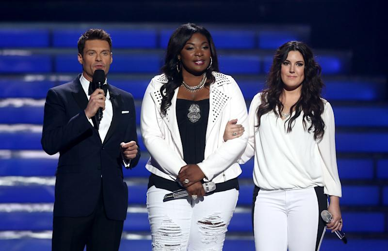 "Host Ryan Seacrest, left, and finalists Candice Glover, center, and Kree Harrison speak on stage at the ""American Idol"" finale at the Nokia Theatre at L.A. Live on Thursday, May 16, 2013, in Los Angeles. (Photo by Matt Sayles/Invision/AP)"