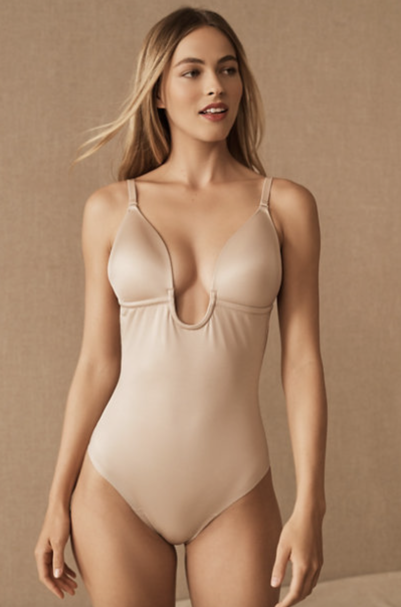 beige spanx plunging neck bodysuit in nude on a model
