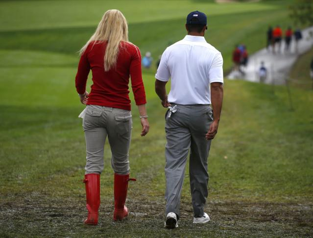 U.S. golfer Tiger Woods walks with his girlfriend Lindsey Vonn after losing his rain delayed Foursome match during the 2013 Presidents Cup golf tournament at Muirfield Village Golf Club in Dublin, Ohio October 6, 2013. REUTERS/Jeff Haynes (UNITED STATES - Tags: SPORT GOLF)
