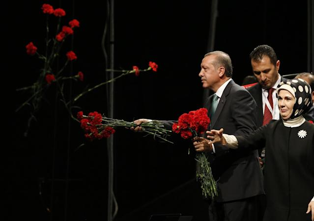 <p>Turkish Prime Minister Tayyip Erdogan throws flowers to his supporters next to his wife Emine during his visit in Cologne May 24, 2014. (Wolfgang Rattay/Reuters) </p>
