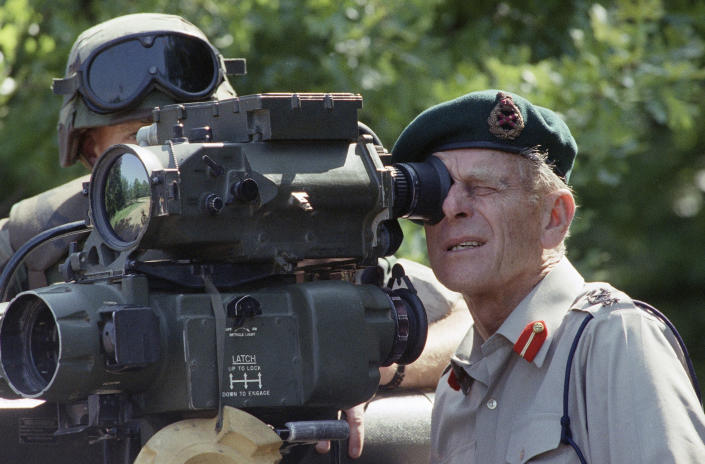 FILE - In this Wednesday, May 15, 1991 file photo, Britain's Prince Phillip squints as he looks through the sight of a TOW missile launcher on at the Quantico Marine Base in Virginia. Buckingham Palace officials say Prince Philip, the husband of Queen Elizabeth II, has died, it was announced on Friday, April 9, 2021. He was 99. Philip spent a month in hospital earlier this year before being released on March 16 to return to Windsor Castle. Philip, also known as the Duke of Edinburgh, married Elizabeth in 1947 and was the longest-serving consort in British history. (AP Photo/Dennis Cook, File)