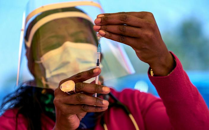 A health worker prepares a dose of the Pfizer coronavirus vaccine at the newly-opened mass vaccination program for the elderly at a drive-thru vaccination center in Johannesburg, South Africa - Themba Hadebe / AP
