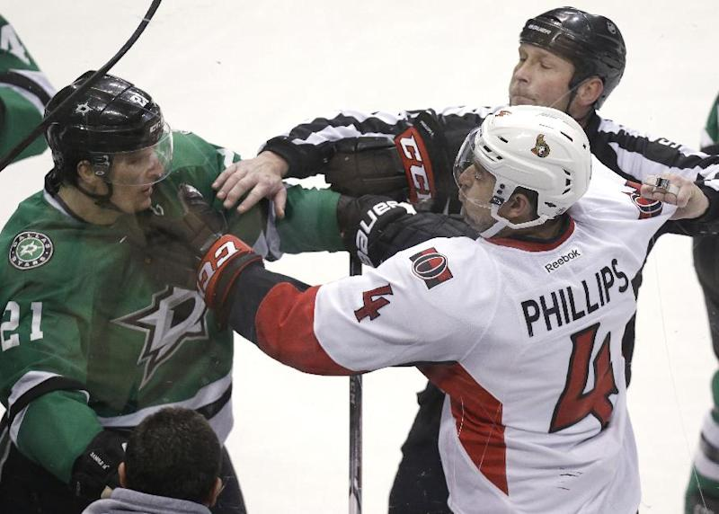 Ottawa Senators defenseman Chris Phillips (4) tangles with Dallas Stars left wing Antoine Roussel (21) as linesman Jay Sharrers tries to break it up during the second period an NHL Hockey game, Saturday, March 22, 2014, in Dallas. (AP Photo/LM Otero)