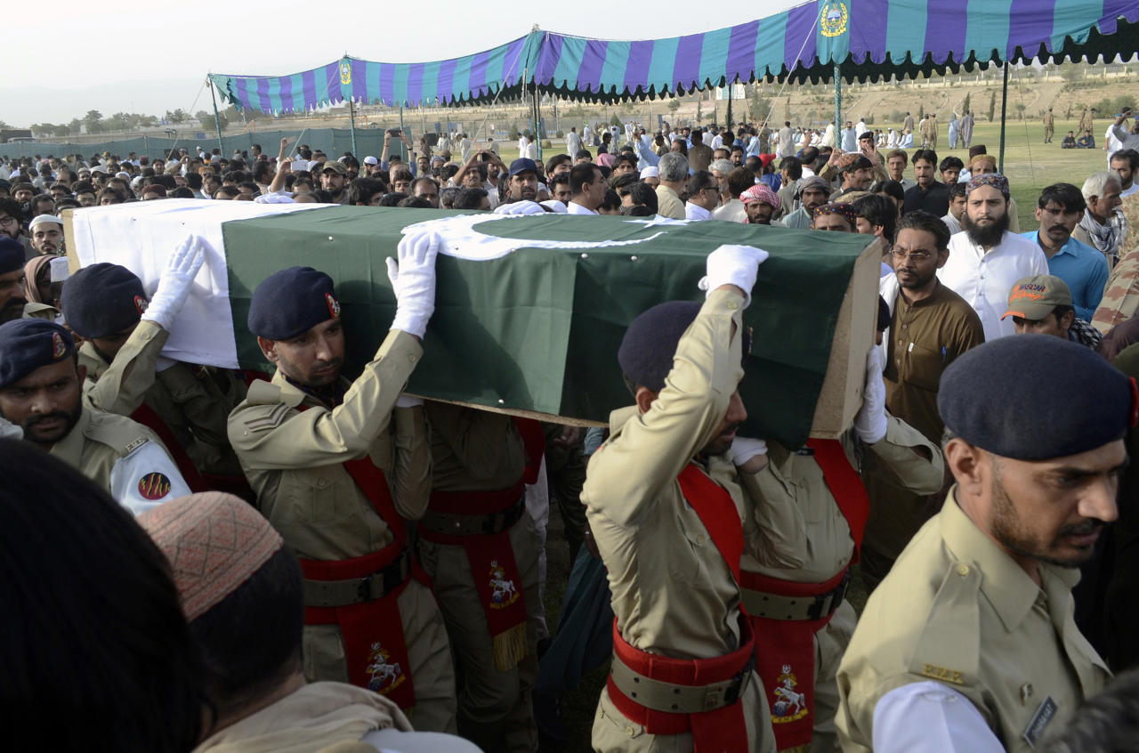 Pakistani troops carry the casket, wrapped in national flag, of provincial candidate Siraj Raisani, who was killed in the Friday's suicide bombing in Mastung, during a funeral prayer in Quetta, Pakistan, Saturday, July 14, 2018. (AP Photo/Arshad Butt)