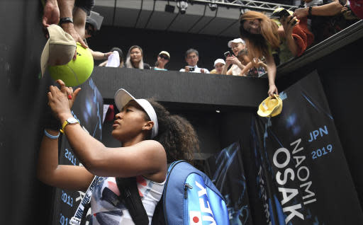 FILE - In this Wednesday, Jan. 22, 2020, file photo, Japan's Naomi Osaka signs autographs after defeating China's Zheng Saisai in their second round singles match at the Australian Open tennis championship in Melbourne, Australia. Osaka has been a Grand Slam champion and No. 1 in the WTA rankings and now shes No. 1 on another list: top-earning female athlete, according to a story posted on Forbes.com on Friday, May 22, 2020. (AP Photo/Andy Brownbill, File)